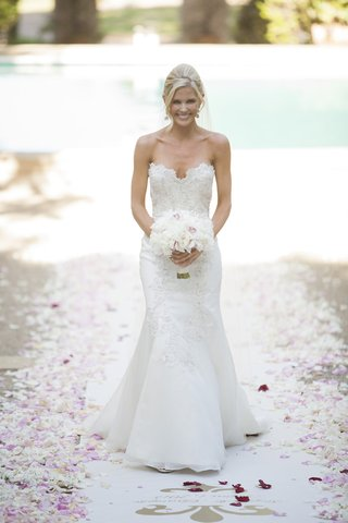 bride-in-white-trumpet-gown-scalloped-neckline-holds-white-pink-bouquet-walking-petal-aisle