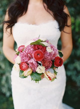 bride-in-gown-holding-pink-and-red-flowers