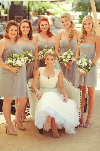 jenna-reeves-in-wedding-dress-armchair-with-five-bridesmaids-in-short-grey-cocktail-dresses