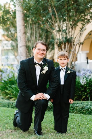 groom-on-one-knee-with-ring-bearer-in-cummerbund-with-black-white-bow-tie-and-tuxedo-suit