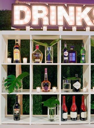 wedding-bar-white-bookcase-bookshelf-alcohol-bottles-monstera-leaves-marquee-sign