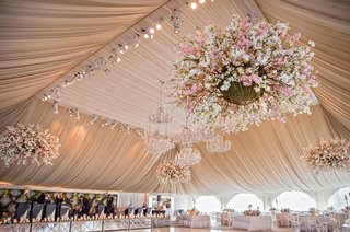 large-reception-ballroom-white-dance-floor-with-chandeliers-draped-ceiling-and-flower-chandeliers