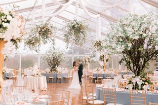 bride-and-groom-photo-in-clear-tent-reception-photo-decor-dogwood-trees-flower-chandeliers-drapery