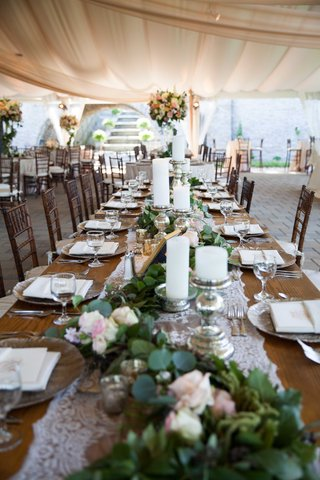 long-wooden-table-with-white-lace-runner-on-top-of-verdant-runner-with-foliage-and-flowers