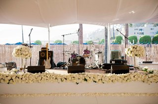 beach-tented-wedding-reception-with-a-raised-stage-bands-intruments-white-roses-hydrangeas