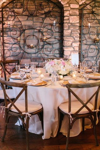 tuscany-inspired-reception-space-with-stone-walls-wrought-iron-details-wooden-chairs