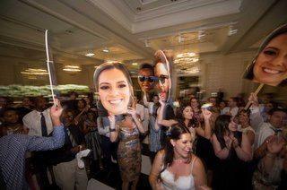 wedding-guests-dance-on-the-dance-floor-with-large-cardboard-cutouts-of-bride-groom-and-ring-bearer