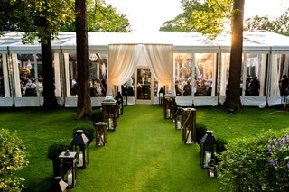 backyard-wedding-lawn-with-wood-lanterns-leading-to-clear-tent-reception-space