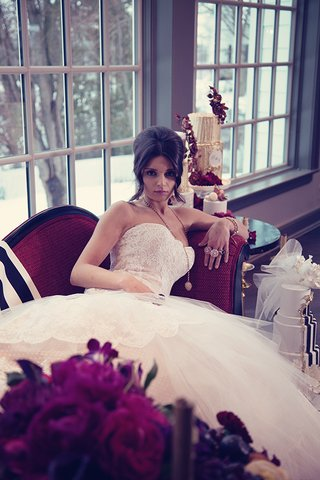 bride-in-a-strapless-lace-gown-with-a-tulle-and-lace-skirt-golden-rings-necklace-and-updo