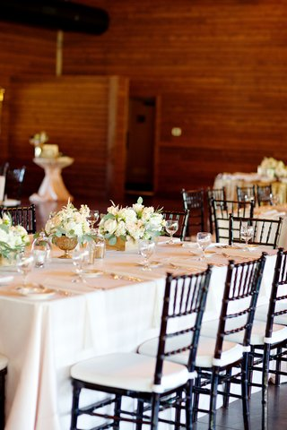 wedding-reception-with-tables-covered-in-white-linens-black-chairs-and-white-flowers