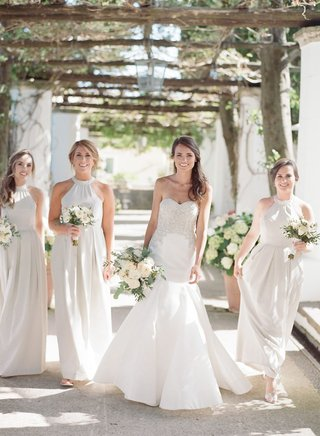 bride-in-strapless-wedding-dress-with-bridesmaids-in-light-color-high-neck-pleated-bridesmaid-dress