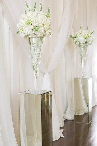 mirrored-pillars-with-white-floral-arrangements-at-front-of-ceremony-space