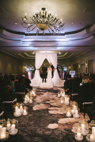candlelit-aisle-leading-to-white-drapery-chuppah-and-light-blue-lighting