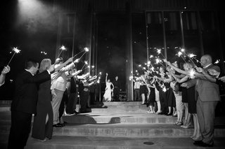 black-and-white-photo-of-bride-and-groom-running-out-of-reception-space-guests-holding-sparkler-exit