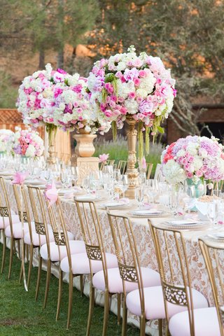outdoor-wedding-reception-table-with-gold-white-damask-tablecloth-golden-chairs-with-pink-cushion
