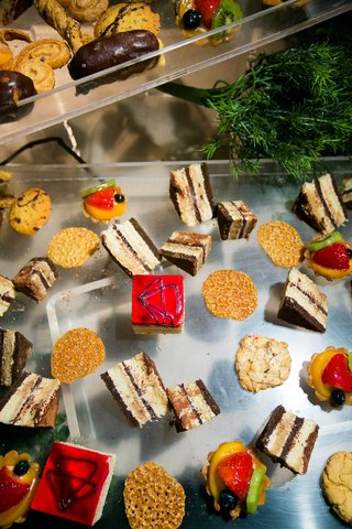 smores-cake-bars-fruit-tarts-and-other-desserts-on-clear-tray-at-wedding-reception