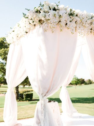 white-drapery-four-post-arbor-alter-with-white-flowers-ties-and-at-top