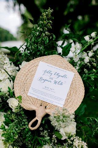 wedding-ceremony-program-on-woven-wicker-rattan-fan-navy-blue-lettering-white-flowers-greenery