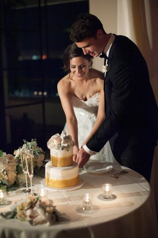 bride-in-strapless-wedding-dress-and-groom-in-tuxedo-cut-two-tiered-white-cake-with-gold-airbrushing