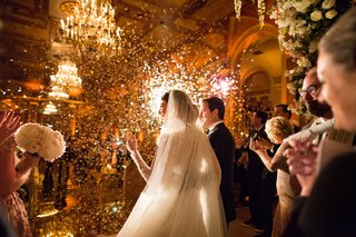 bride-and-groom-looking-out-to-audience-guests-at-wedding-ceremony-confetti-and-lights-shining