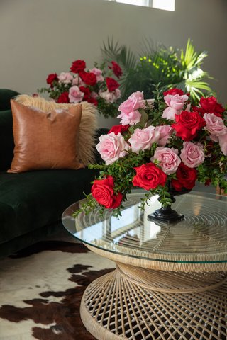 small-arrangement-of-pink-roses-and-red-roses-on-glass-top-wicker-woven-tables