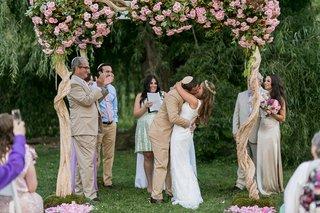 bride-and-groom-kiss-at-garden-wedding-altar