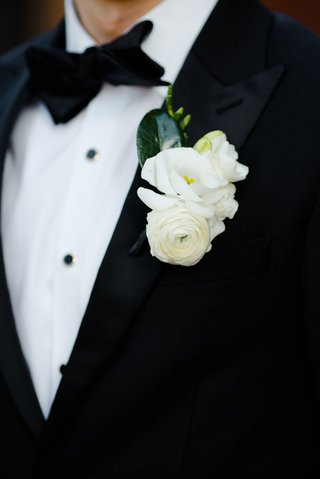 groom-in-tuxedo-with-multiple-white-flower-boutonniere-including-ranunculus-black-bow-tie-green-leaf