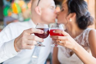 bride-and-groom-kiss-at-restaurant-with-craft-cocktails-red-libations-engagement-ring-pear-shape