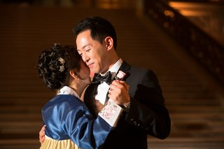 korean-mother-in-hanbok-with-blue-bodice-gold-skirt-dances-with-groom-in-black-tux-at-wedding