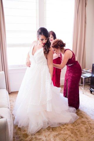 bridesmaids-in-wine-hued-dresses-help-bride-into-hayley-paige-wedding-dress