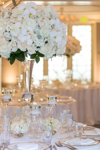 close-up-of-tall-white-wedding-centerpiece-rose-hydrangea-rochid-flowers-and-green-leaves