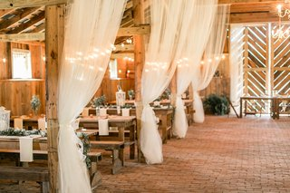 wood-wedding-reception-barn-white-sheer-drapery-brick-floor-wood-picnic-tables-greenery-lantern