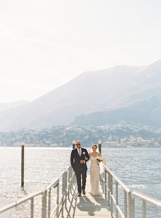 wedding-portrait-bride-and-groom-arm-in-arm-walking-up-dock-lake-como-italy-destination-wedding