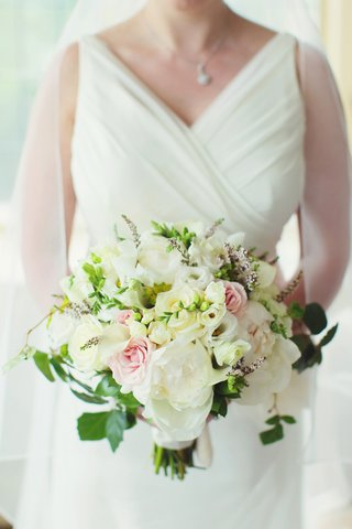 bride-in-v-neck-wedding-dress-holding-flowers