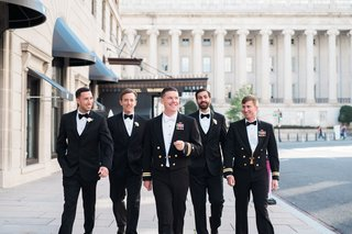groom-in-navy-uniform-with-white-bow-tie-with-groomsmen-in-tuxedos-and-bow-ties-with-one-in-uniform