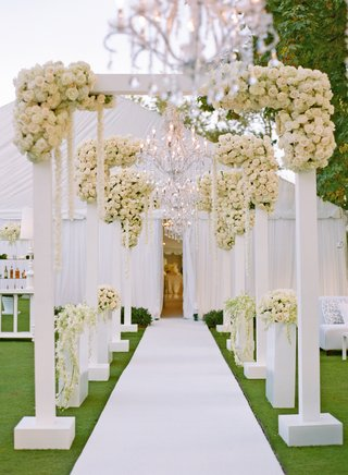 white-arches-and-roses-on-path-to-tent-wedding-reception