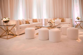 wedding reception lounge area white carpet ballroom white ottoman gold glass accent table flowers