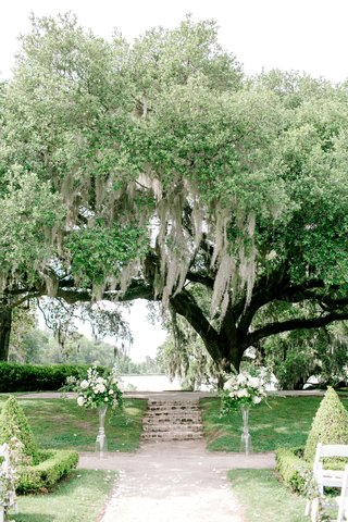 wedding-ceremony-in-south-carolina-white-flower-greenery-on-both-sides-of-vow-exchange-spot-shrubs