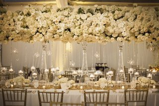 wedding-reception-table-with-tall-arrangements-of-white-roses-hydrangeas-and-orchids-crystals