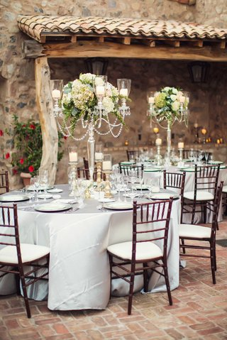 silver-tablecloth-candelabra-centerpiece-with-crystals-antique-green-hydrangea-flowers-candles-stone