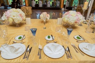 blue-toasting-glasses-for-bride-and-groom-at-gold-head-table