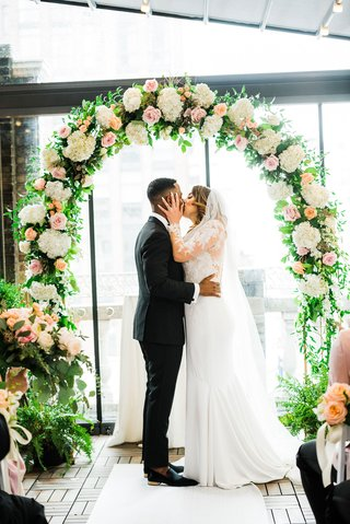 bride-grabs-groom-by-the-face-for-first-married-kiss-under-floral-arch