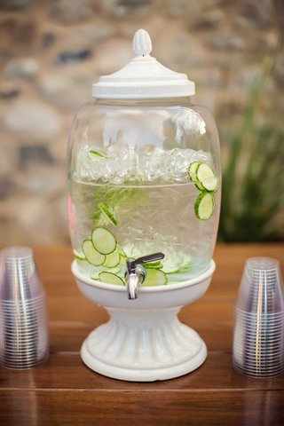 white-drink-dispenser-with-silver-spout-ice-water-with-sliced-cumbers