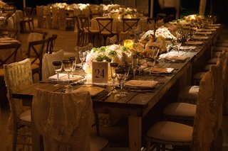 wood-farm-table-at-wedding-reception-with-lace-chair-covers