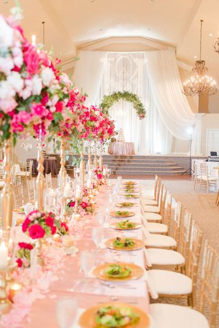wedding-reception-ballroom-cake-on-display-lighting-projection-stage-pink-centerpiece-gold-stands