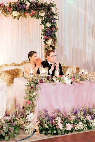 interfaith-wedding-bride-groom-on-throne-settee-purple-green-color-palette-drift-wood-air-plant