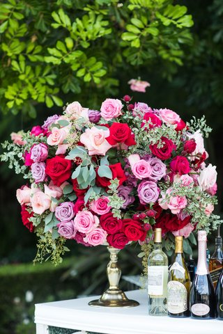 wedding-reception-cocktail-hour-bar-with-flower-arrangement-greenery-pink-rose-red-lavender-greenery