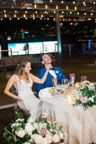 bride-in-lace-dress-and-groom-in-bright-blue-suit-laughing-while-sitting-at-their-sweetheart-table