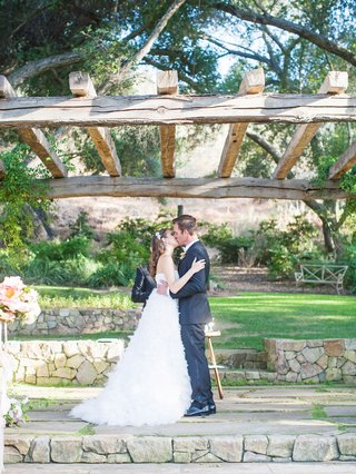 bride-in-monique-lhuillier-wedding-dress-kisses-groom-at-outdoor-ceremony-in-vista-california-rocks