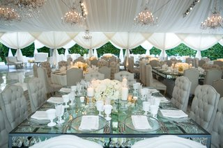 tented-wedding-reception-square-glass-table-with-crystals-in-between-layers-tufted-beige-chairs